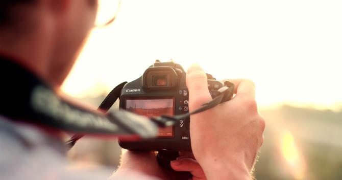 Bilden föreställer en DSLR, digitalkamera som hålls upp mot solnedgången