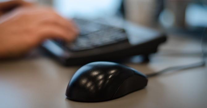 Datormus i förgrunden, ett tangentbord och händer i bakgrunden.