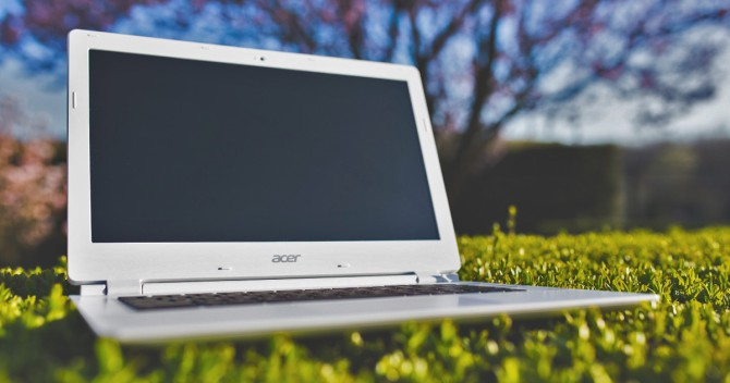 Bärbar dator från Acer med WiFi på gräsmattan. Det kan vara konstgräs.