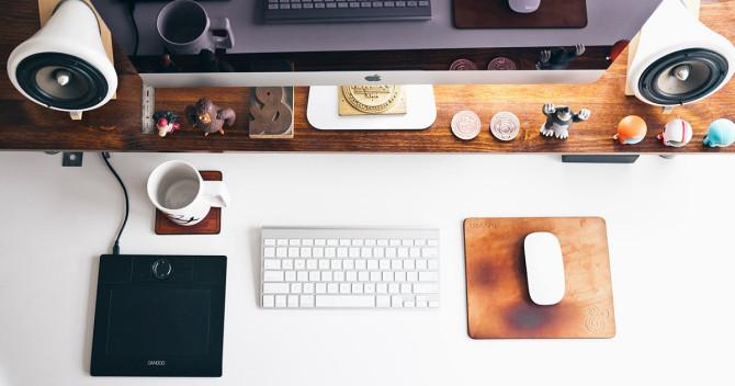 Ett skrivbord med en iMac-dator, tangentbord och mus samt en ritplatta