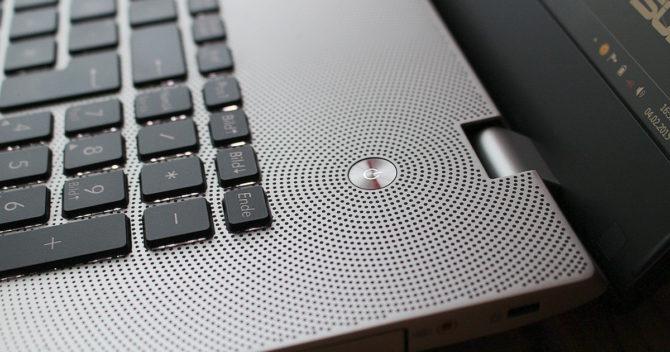 Högtalarens hål på en bärbar dator bildar ett vackert geometriskt mönster runt batterier.