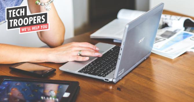 En kvinna använder en laptop på ett bord av trä. På bordet ligger även en telefon och en surfplatta.