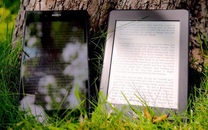 En Sony Z Ultra tablet och en Amazon Kindle Paperwhite står mot ett träd i solljus. Det går knappt att se vad det står på Sonyn, men texten på Kindle är tydlig.
