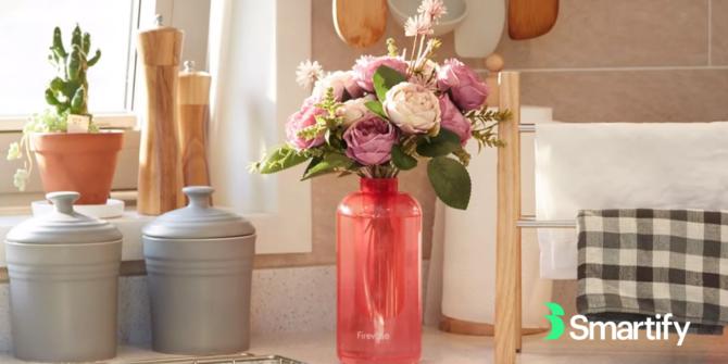Rosa blomvas i ett kök